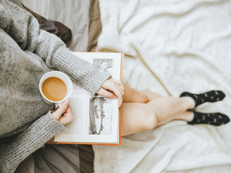 Woman reading in bed with mug of coffee