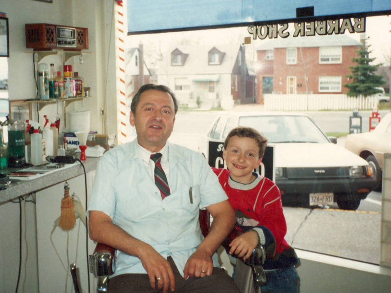 Young Chris Grafos with his father in the family barber shop